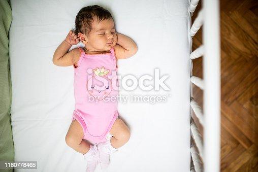 Newborn baby girl peacefully sleeping in the crib. High angle view.