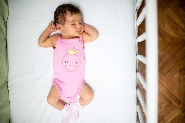 What a wonderful life! Newborn baby girl peacefully sleeping in the crib. High angle view. crib stock pictures, royalty-free photos & images