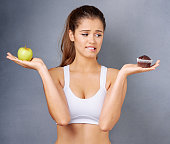 Studio shot of a young woman choosing between healthy and unhealthy foods against a grey background