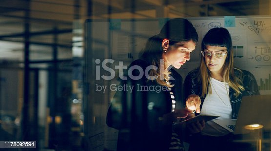 Cropped shot of two attractive young businesswomen standing together and using technology to brainstorm in the office at night