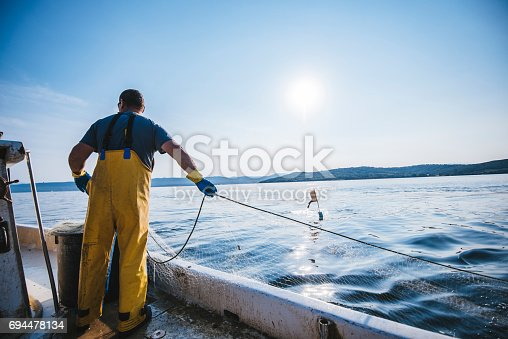 Fisherman putting the fishing net into the water. He is standing on his boat. Sun in back.