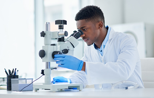 Cropped shot of a focused young male scientist looking at test samples through a microscope inside of a laboratory during the day