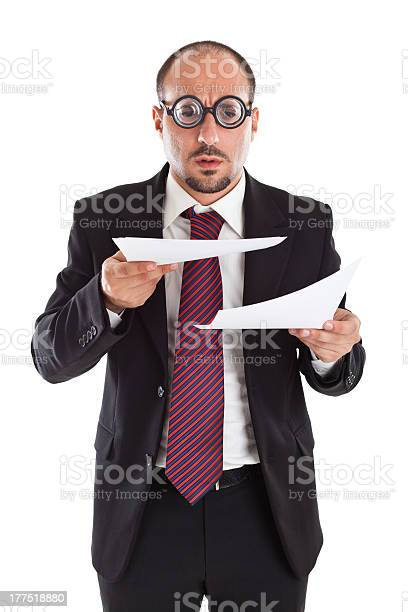 """A businessman wearing thick, circle glasses tryng to read some documents"""