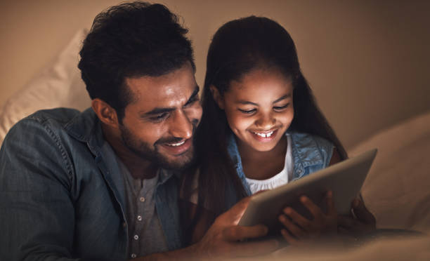 What better way to bond than with digital bedtime stories stock photo