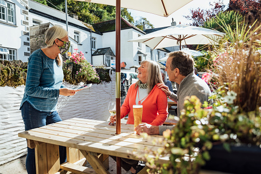 A couple sitting at a wooden table in a beer garden in Polperro, Cornwall, drinking alcoholic drinks. A waitress is taking their order at their table using a digital tablet, she is wearing a protective face mask to reduce the spread of Coronavirus during the COVID-19 pandemic.