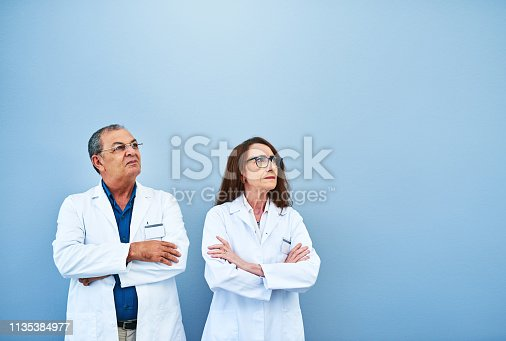 Studio shot of two scientists looking up against a blue background