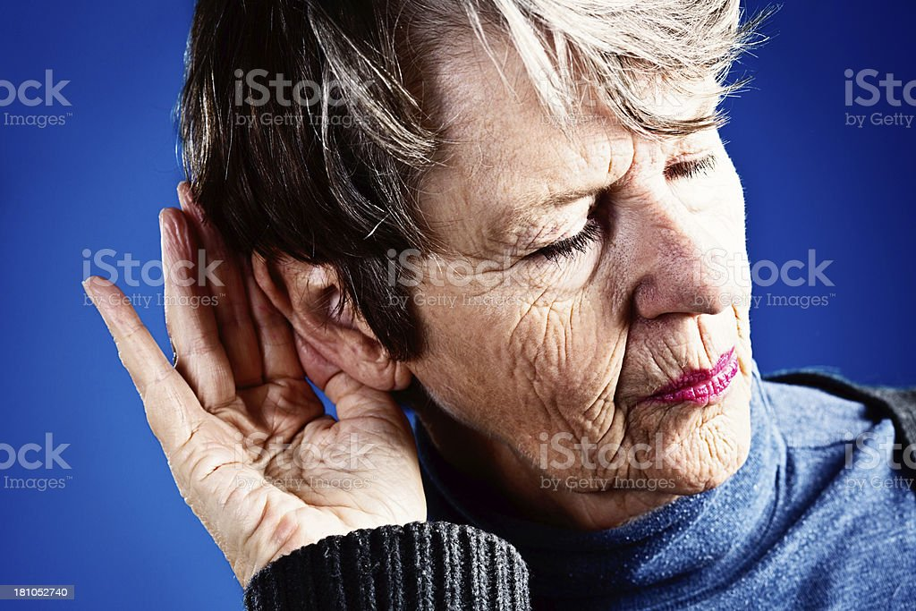 What? Deaf old woman cups hand round ear royalty-free stock photo