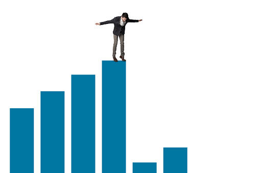 Shot of a businessman about to jump from the edge of a graph against a white background