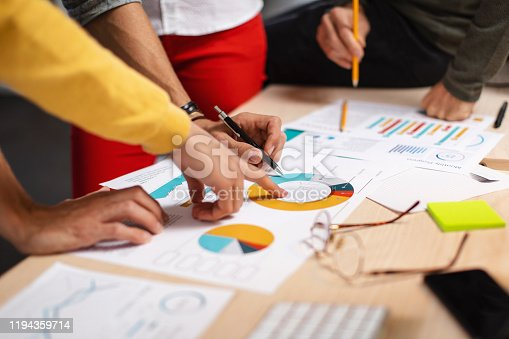 Close-up shot of a group of colleagues going through paperwork together in the office
