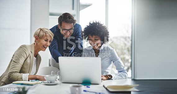 Cropped shot of a diverse group of businesspeople using a laptop during a meeting in the office