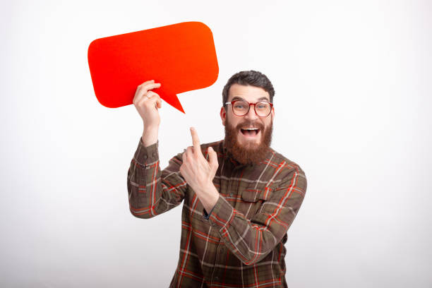 what does it say, bearded man is pointing at a red bubble speech he is holding. - feedback icon imagens e fotografias de stock