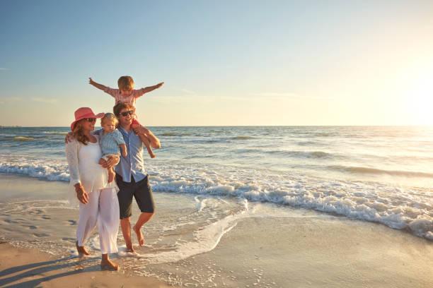 qué buen tiempo para pasear por la playa - vacaciones familiares fotografías e imágenes de stock