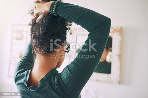 Rearview shot of a young woman tying her hair in the bathroom at home