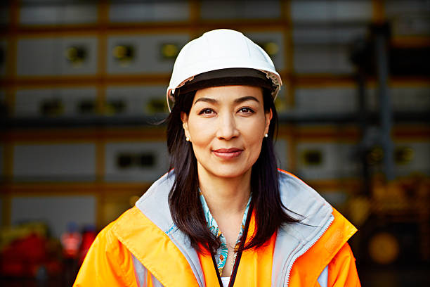 What happens on this dock is my responsibility Portrait of a woman in workwear standing on a commercial dock hardhat stock pictures, royalty-free photos & images