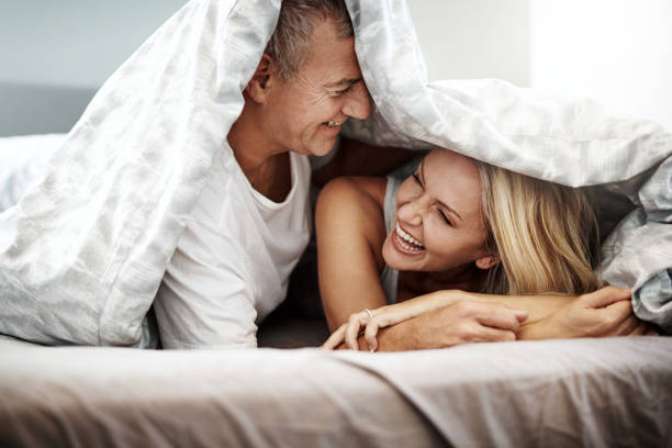 What happens under the covers, stays under the covers Shot of an affectionate couple spending the day in bed couple in bed stock pictures, royalty-free photos & images