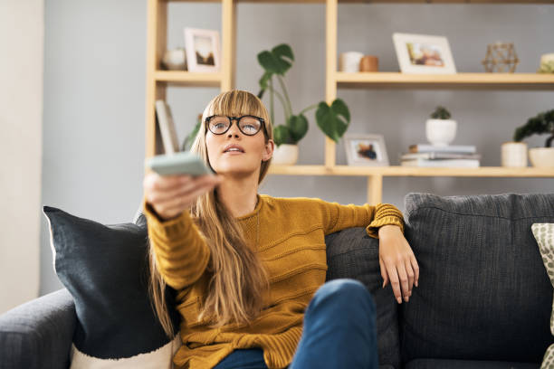 What have I missed out on this week? Shot of a young woman watching television on the sofa at home changing channels stock pictures, royalty-free photos & images
