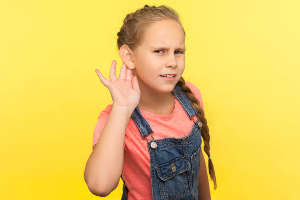 What? I can't hear! Portrait of curious attentive little girl in denim overalls holding hand near ear What? I can't hear! Portrait of curious attentive little girl in denim overalls holding hand near ear and listening carefully intently to what you say. indoor studio shot isolated on yellow background nerd hairstyles for girls stock pictures, royalty-free photos & images