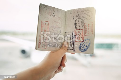 POV shot of an unrecognizable woman holding a passport indoors