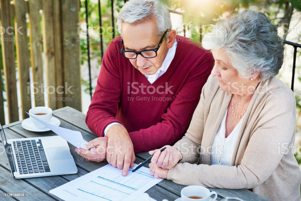 What if we moved this around? Cropped shot of a senior couple going over their finances while sitting outside on the veranda 70-79 Years Stock Photo
