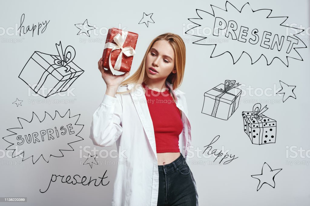 What is inside? Attractive young woman is holding a gift box and...