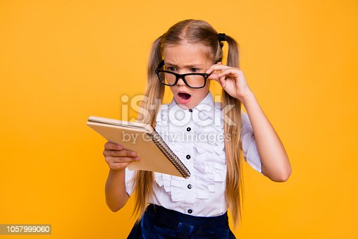 531869550 istock photo What is it! I do not understand it! Close up photo portrait of sad angry annoyed upset schoolkid with open mouth adjusting glasses staring looking at copybook textbook isolated bright background 1057999060