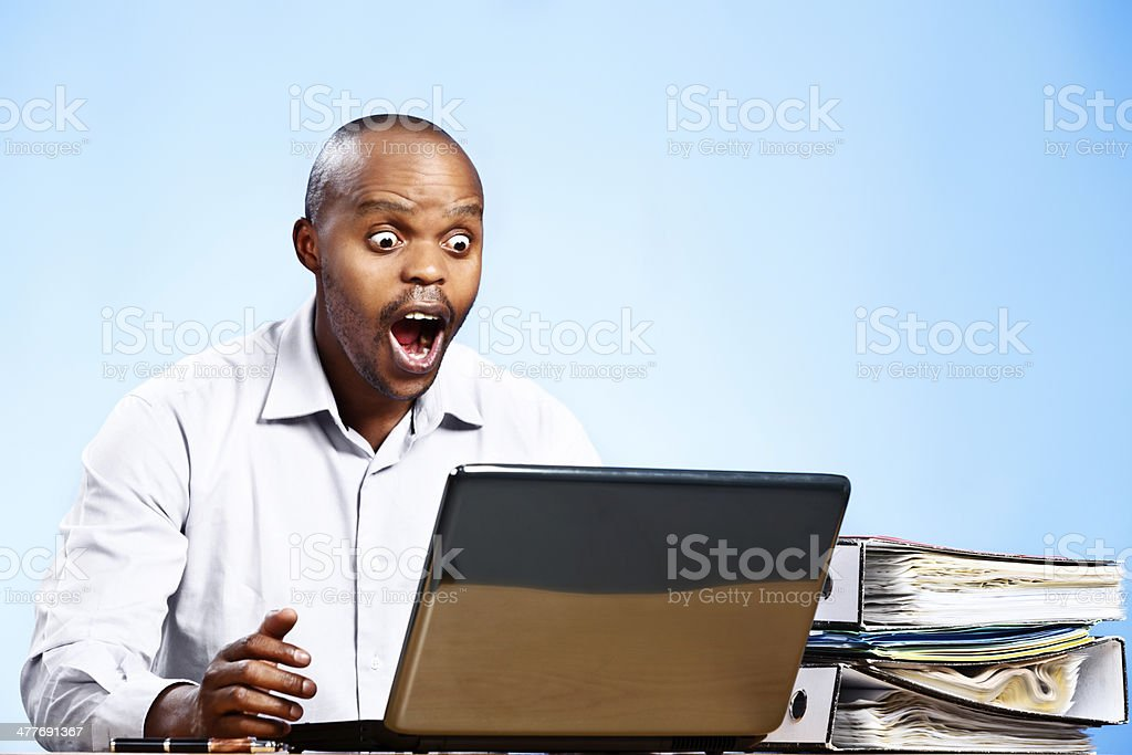 What is that? Horrified businessman looks at laptop screen goggle-eyed stock photo