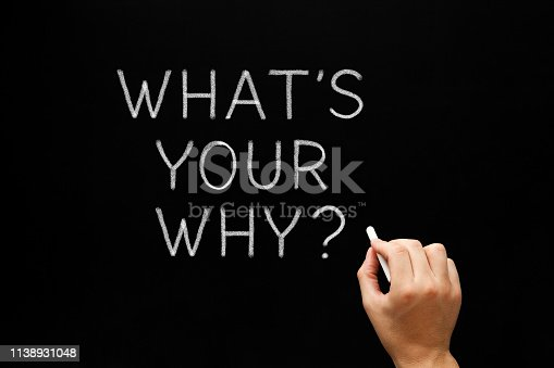 Hand writing What Is Your Why existential question with white chalk on blackboard.
