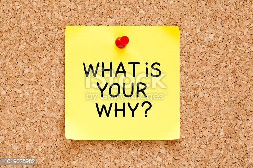 What is your why question handwritten on yellow sticky note pinned on cork bulletin board.