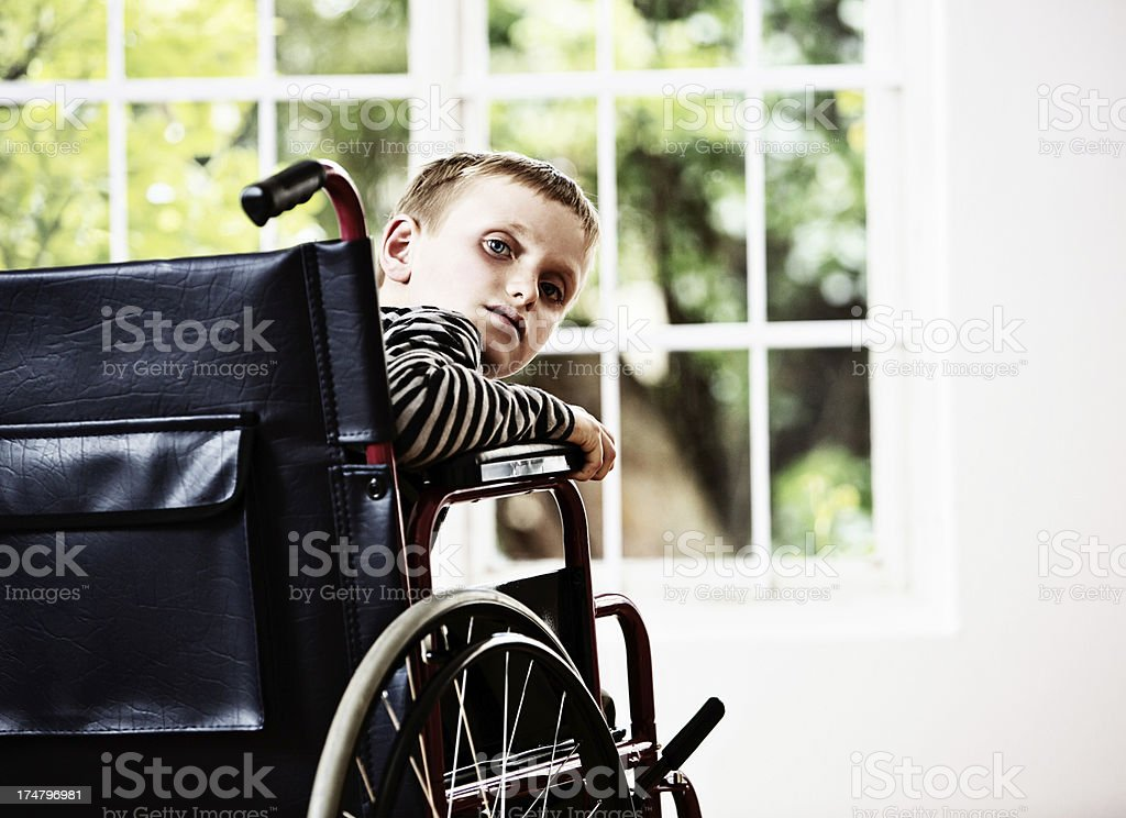 What now? Frail, unhappy boy in wheelchair frowns over shoulder stock photo
