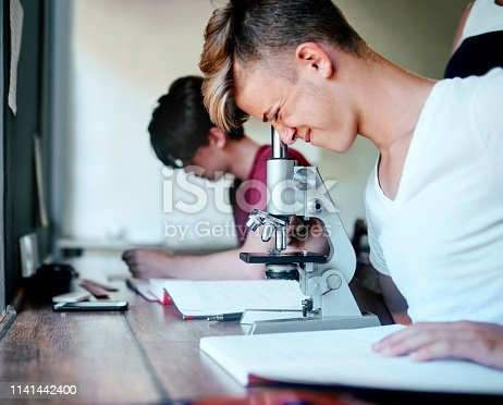 Cropped shot of a focused young student looking through a microscope while being seated at his desk at school