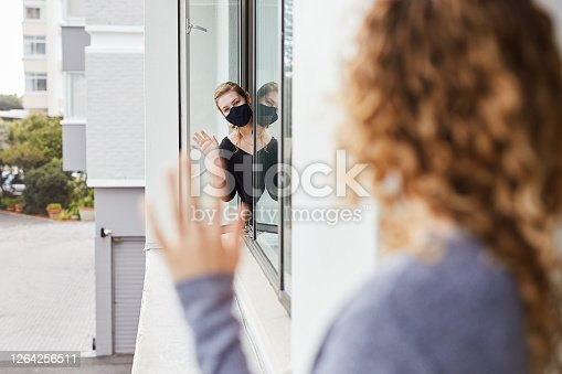 Shot of two women waving at each other from their apartment's