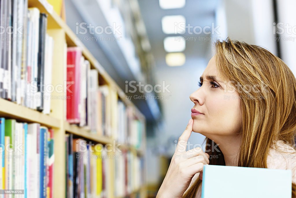What shall I read today? Pretty woman choosing library books royalty-free stock photo