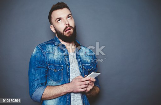 825083556istockphoto What should I write to you? A handsome young bearded man in a denim shirt writes a message in the phone on a gray background. 910170394