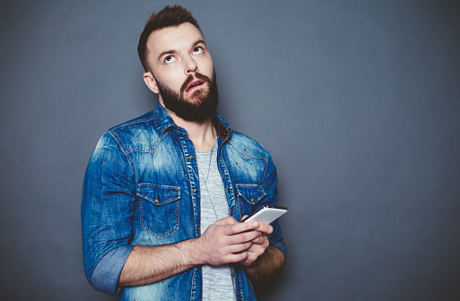 825083556 istock photo What should I write to you? A handsome young bearded man in a denim shirt writes a message in the phone on a gray background. 910170394