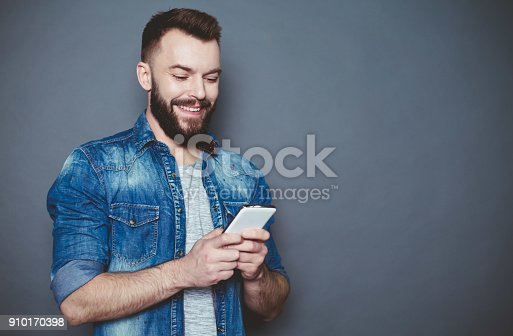 825083556istockphoto What should I write to you? A handsome young bearded man in a denim shirt writes a message in the phone on a gray background. 910170398