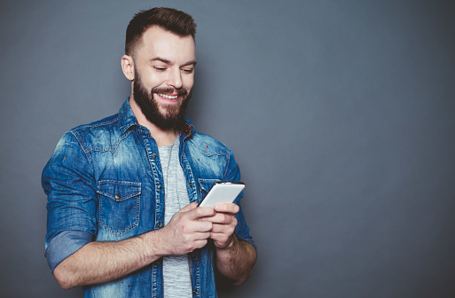825083556 istock photo What should I write to you? A handsome young bearded man in a denim shirt writes a message in the phone on a gray background. 910170398