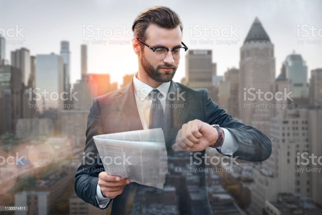 What time is it? Business expert holding popular newspaper and looking at his watch while standing against of morning cityscape background stock photo