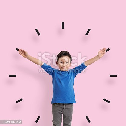 6-7 years old child standing in front of pink wall. His arms are open like clock.