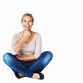 A beautiful young woman sitting down and looking happy while isolated on white