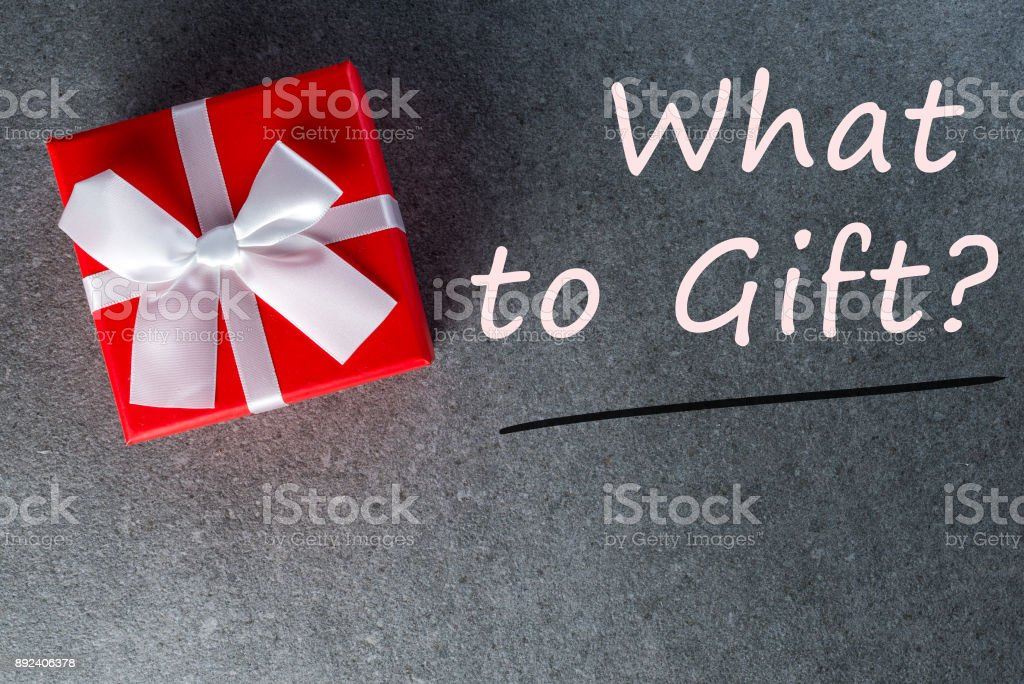 What to Gift? - Nice Christmas gift wrapped in red gift paper with white bow on dark background. New Year, holidays and celebration concept stock photo