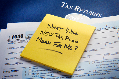 A yellow sticky pad rests on top of a U.S. 1040 income tax return and asks the question as to what the new tax plan would mean for me?