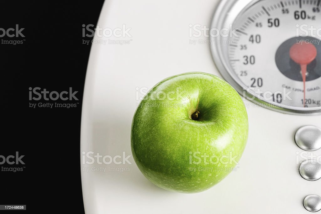 What you eat determines your weight: apple rests on scale royalty-free stock photo