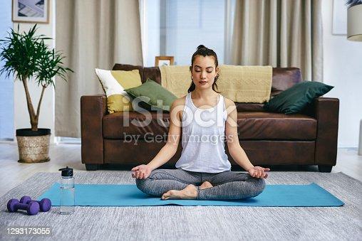 Shot of a young woman meditating at home