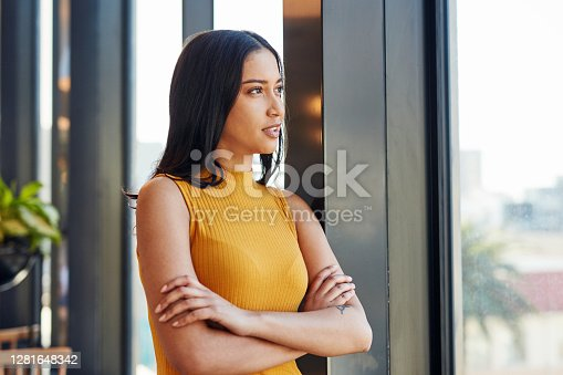 Shot of a young businesswoman looking thoughtfully out of a window in a modern office