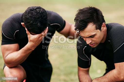 Shot of two young men looking upset while playing a game of rugby