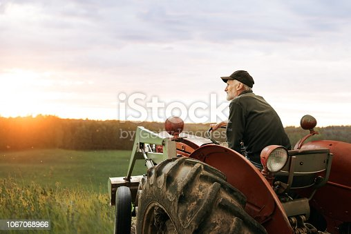 Shot of a man operating a tractor on a farm