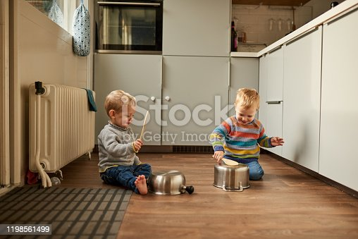 Shot of two adorable young brothers banging on pots and pans in the kitchen at home
