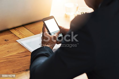 Cropped shot of a businessman using a mobile phone at his desk