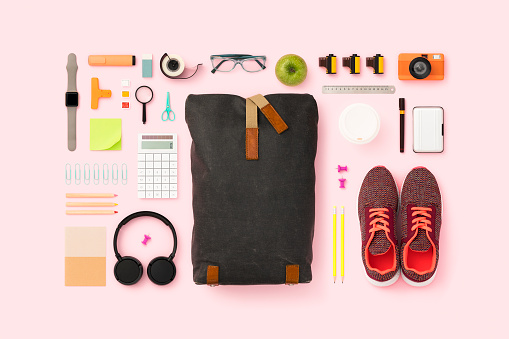 School supplies and backpack flat lay. Back to school flat lay on pink background