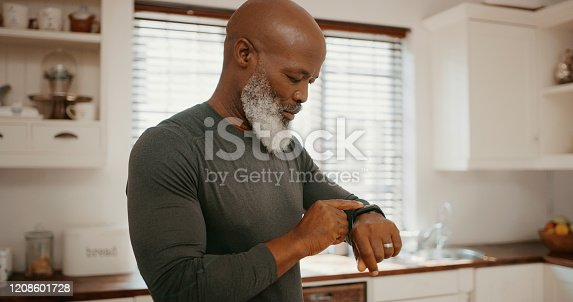 Cropped shot of a senior man standing and checking his fitness tracker after a workout